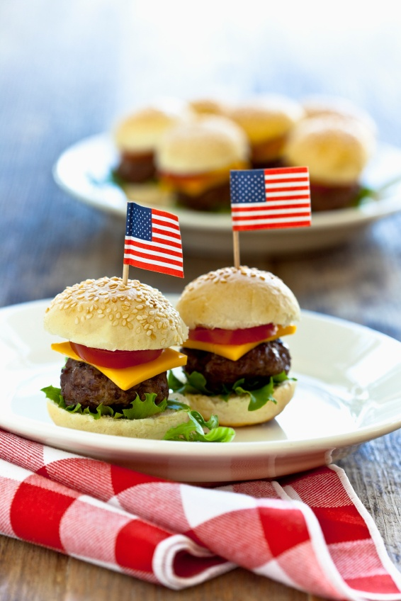 Mini hamburgers with American flags on wooden table.